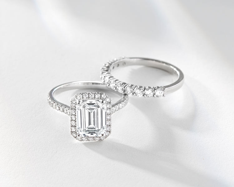Bridal Set Including the Ecksand Pavé Emerald Cut Diamond Halo Engagement Ring with Diamond Band and Ecksand Pavé Semi Eternity Diamond Pavé Wedding Ring on White Table