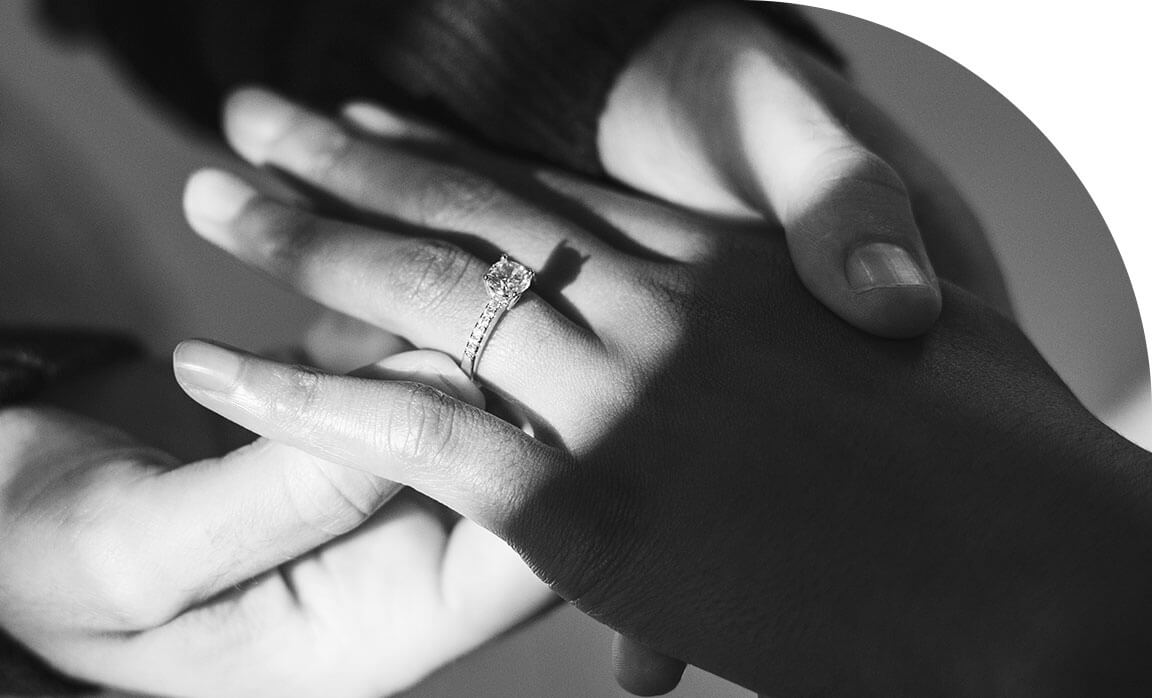 A Person Placing the Ecksand Pavé Round Diamond Engagement Ring with Diamond Band on Their Fiancée's Finger in Proposal